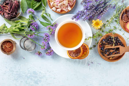 Tea, overhead shot with copy space. Herbs, flowers and fruit around a cup of tea