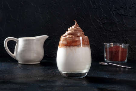 Dalgona cold coffee with ingredients and copy space, on a black slate background 版權商用圖片