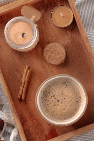 Hygge. Breakfast tray with coffee and scented candles, overheaed flat lay shot on a warm blanket