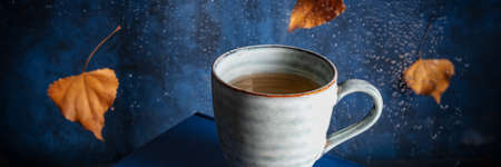 Autumn panorama with a cup of tea and falling leaves behind a window with raindrops