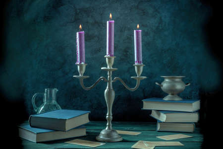 Magic and divination. Purple candles, magick potions, divination cards and occult books