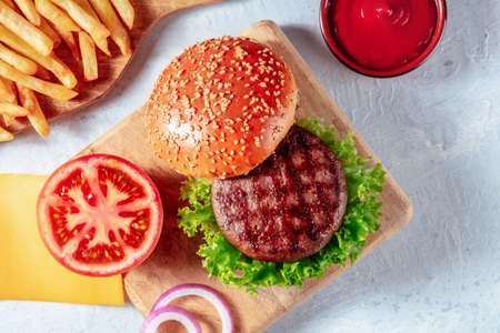 Hamburger ingredients, shot from above with French fries and ketchup, on a rustic wooden board