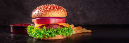 Burger panorama on a black background with copy space. Beef patty steak with a salad leaf, cheese, vegetables, and a sesame bun, with ketchup