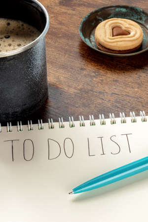 To Do List, handwritten words on a paper notepad, with a turquoise blue pen and a coffee mug, on a wooden desk, with a cookie