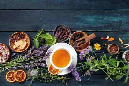 A cup of tea with dry fruit, flowers, and herbs, shot from above on a dark rustic wooden background with copy space