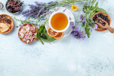 Herbal tea, top shot with copy space. Herbs, flowers and fruit around a cup of tea