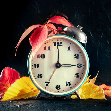 Daylight Saving Time concept, fall back one hour in autumn. A vintage alarm clock with autumn leaves on a black background, square image 版權商用圖片