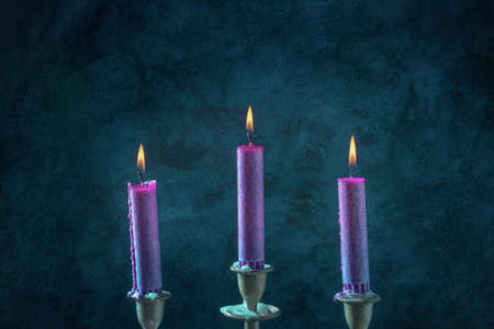Candle magic. Purple candles burning on a dark blue background, toned image, with a place for text