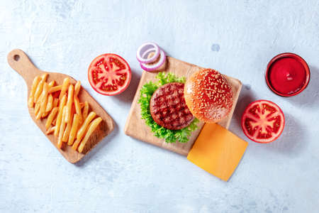 Burger ingredients, overhead flat lay shot. Hamburger patty steak, French fries, vegetables and ketchup, shot from the top