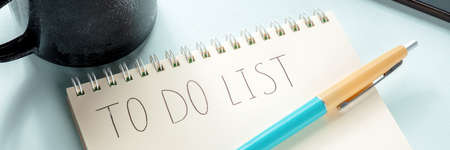 To do list panorama. A paper notepad with a coffee mug and a blue pen. The concept of planning, time management etc