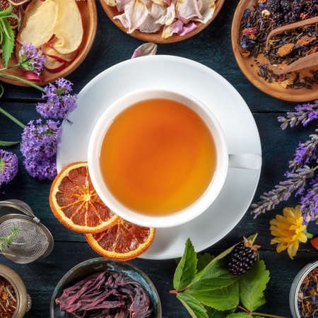 Tea, overhead square shot. Leaves, flowers and fruit around a cup of tea on a dark rustic wooden background