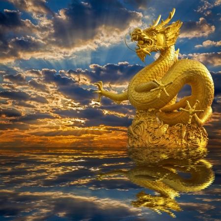 dragones: China Golden Dragon Estatua con la puesta del sol Foto de archivo