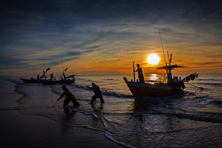 silhouet van de visser met zonsopgang in de achtergrond