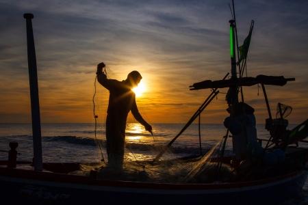 silhouet van visser met zonsopgang op de achtergrond