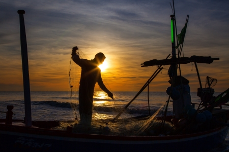 silhouette of fisherman with sunrise in the background  Stock Photo