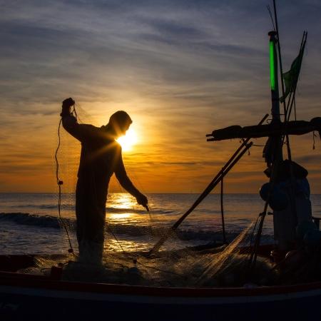 バック グラウンドで日の出と漁師のシルエット 写真素材