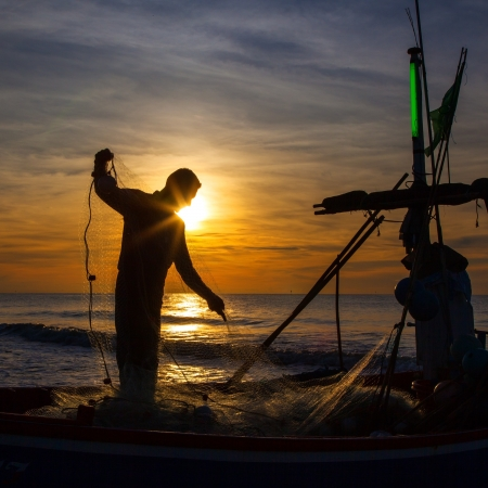 silhouette of fisherman with sunrise in the background  Imagens