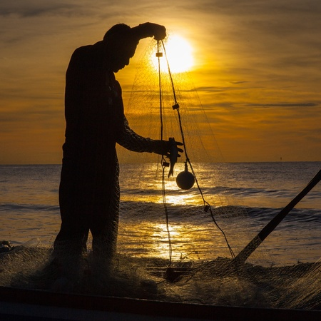 nets: silhouette of fisherman with sunrise in the background