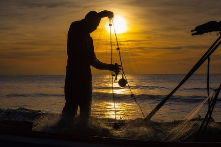 silhouette of fisherman with sunrise in the background Stock Photo - 18195783