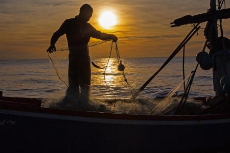 redes de pesca: silueta del pescador con la salida del sol en el fondo