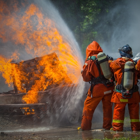 Firefighter fighting For A Fire Attack, During A Training  Reklamní fotografie