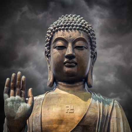 natural landmark: The statue of Big Buddha face with hand in Hongkong on  storm clouds background  Stock Photo