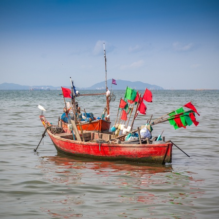 Traditional fishing boat anchoring near a beach  photo