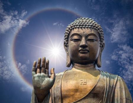 현상: 환상적인 아름 다운 태양 후광 현상의 배경에 홍콩에서 손으로 큰 부처님 얼굴의 동상 스톡 사진