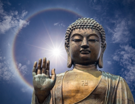 The statue of Big Buddha face with hand in Hongkong on fantastic beautiful sun halo phenomenon background
