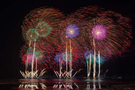multiples: Fireworks of multiples colors with reflections on water Stock Photo
