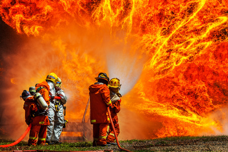 Firefighters fighting fire during training  Stockfoto