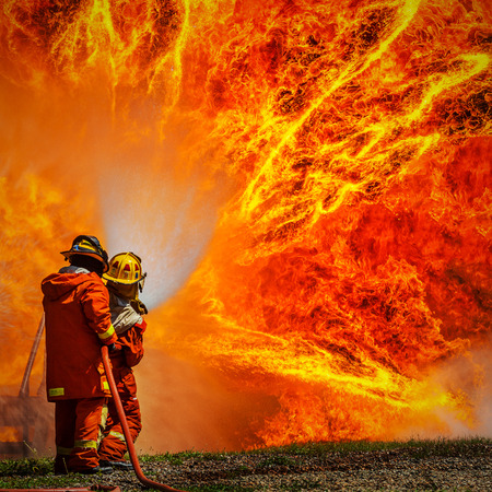 Firefighters fighting fire during training  Imagens