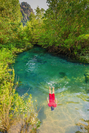 Boy wearing a red dress re Diving in Tha pom nature Crystal stream, Krabi, Thailand  photo