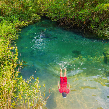 thapom: Boy wearing a red dress re Diving in Tha pom nature Crystal stream, Krabi, Thailand  Stock Photo