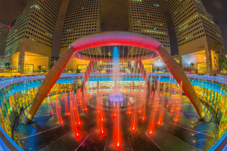 SINGAPORE-AUG 30: Fountain of Wealth with Suntec Towers at dusk on August 30,2014 in Singapore. Fountain of wealth is the biggest fountain in Singapore located Suntec Towers, SINGAPORE.