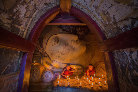 BAGAN, MYANMAR - JAN 15,2015: Unidentified young Buddhism monks praying with candle light at Shwesandaw temple on January 15, 2015 in Bagan, Myanmar. Buddhism is predominantly of the Theravada tradition, practised by 89% of the population.