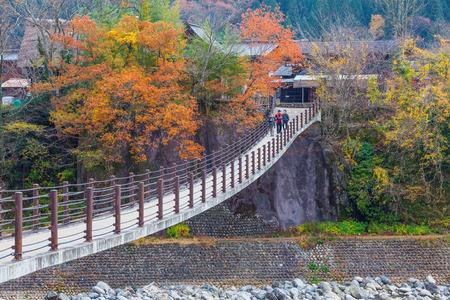 ogimachi: SHIRAKAWA GO, JAPAN - NOV. 12, 2014 : Unidentified people cross the bridge over Shogawa river to the Ogimachi Village, one of Japans UNESCO world heritage sites in Shirakawa Go, Japan.