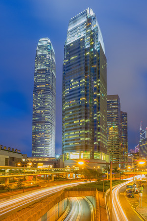 back in an hour: Hong Kong Business District at Night. Corporate building at the back and busy traffic across the main road at rush hour.