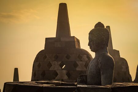 Buddha statue in open stupa in Borobudur, or Barabudur, temple Jogjakarta, Java, Indonesia at sunrise. It is a 9th-century Mahayana temple and the biggest Buddhist Temple in Indonesia.