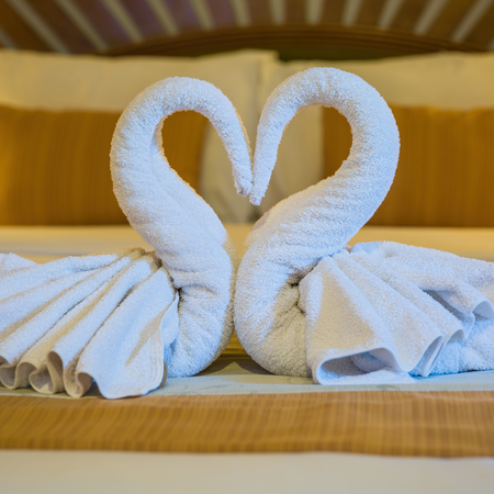 Swans made from towels on the bed Imagens