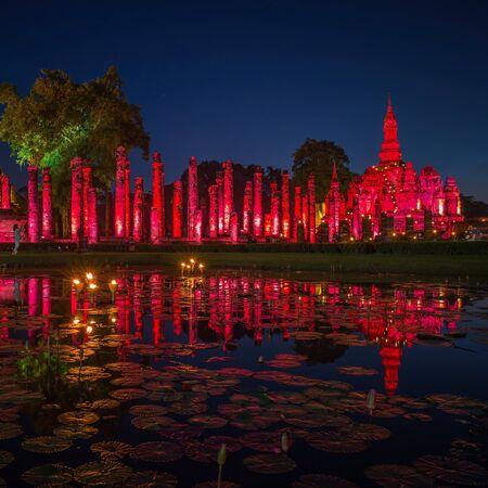 Light up night of Wat Maha That Buddha and pagoda on sunset time. Sukhothai historical park temple, Thailand. Banco de Imagens