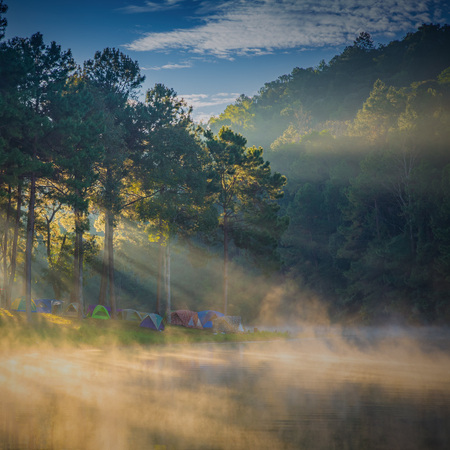 Dome tents beside the lake in the mist at sunrise at Pang Ung (Pang Tong reservoir), Mae Hong Son province, Thailand