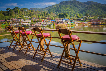 Lonely empty chairs on a deck at rak Thai Village in Mae Hong Son province, Thailand. for traveler to sit and relax. Travel and Relax concept. Stock Photo