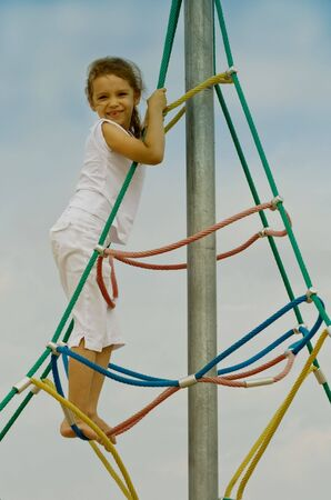5 years old Little girl playing outdoor climbing photo