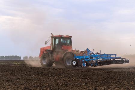 arando: tractor arando la tierra.