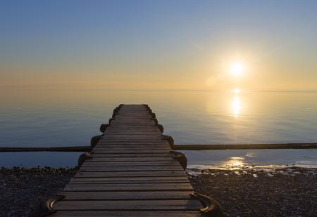 Wooden pier sea sunset. 免版税图像