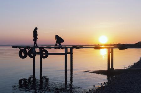 people on the bridge at sunset
