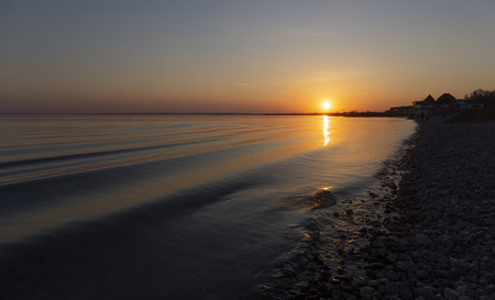 wave rolls on the beach sunset.