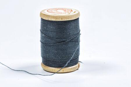 Black thread on a wooden spool.