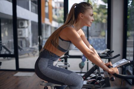 Young beautiful girl on an exercise bike in a gym. Cycling Zdjęcie Seryjne